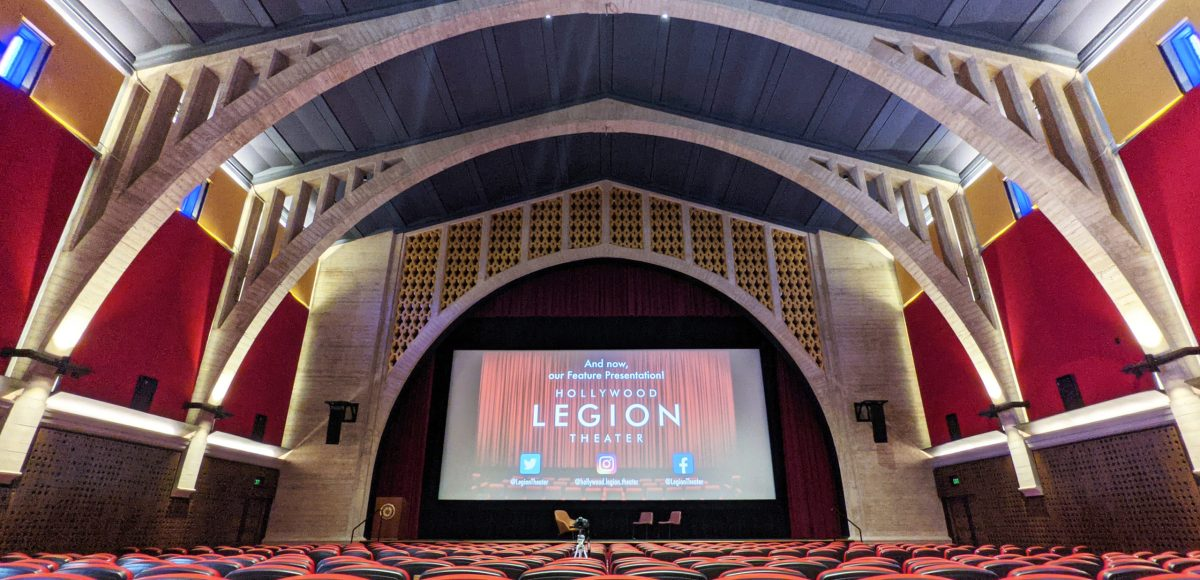 a movie theater's screen, with arched ceilings and seats in front