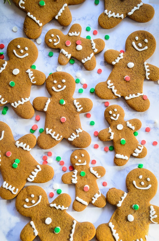 Large and small  decorated gingerbread cookies scattered across a cookie sheet with green, white and red sprinkles.