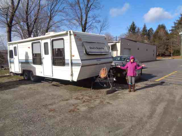 Liz looks disgusted in front of a small camper