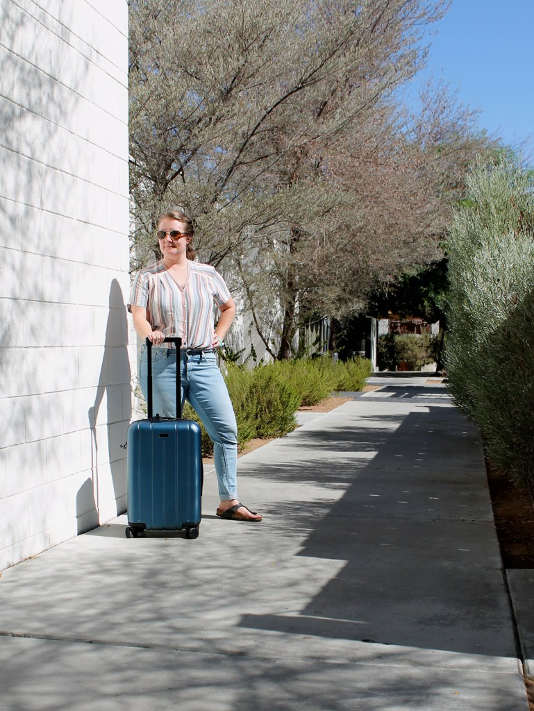 Desert scene of blogger in pastel colors standing next to CHESTER small carry-on size bag.