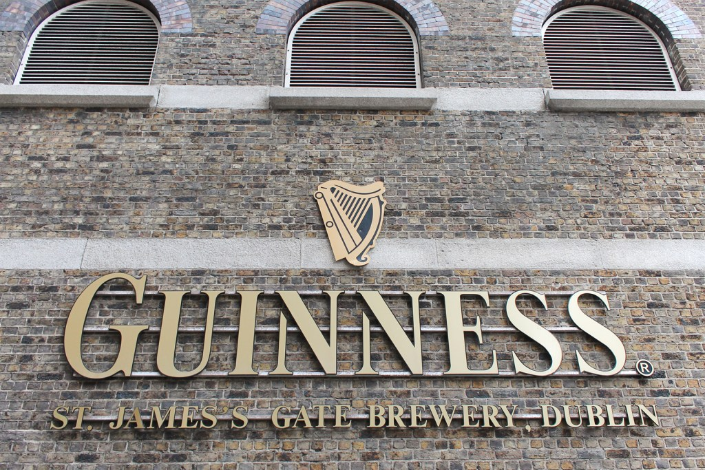 Guinness logo in gold affixed to a grayish brown brick building.
