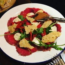 Beef carpaccio with roasted capsicum, truffle aioli, rocket and parmesan chips