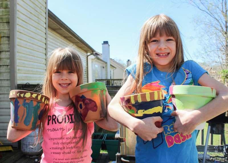 kids painting ceramic pots and gardening