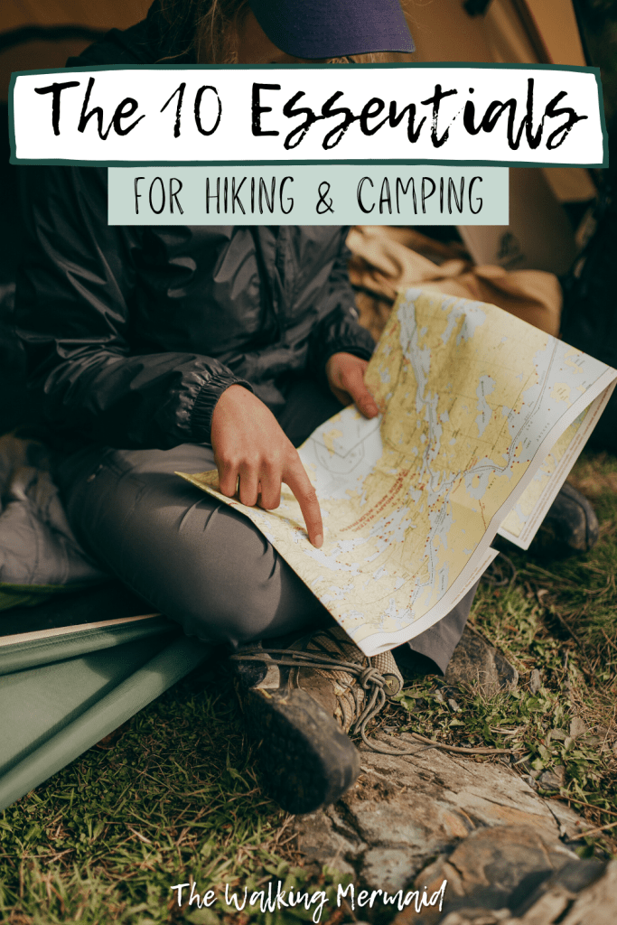 Woman pointing at a map sitting in her tent. Posted on a blog post that talks about the ten essentials for camping and hiking.
