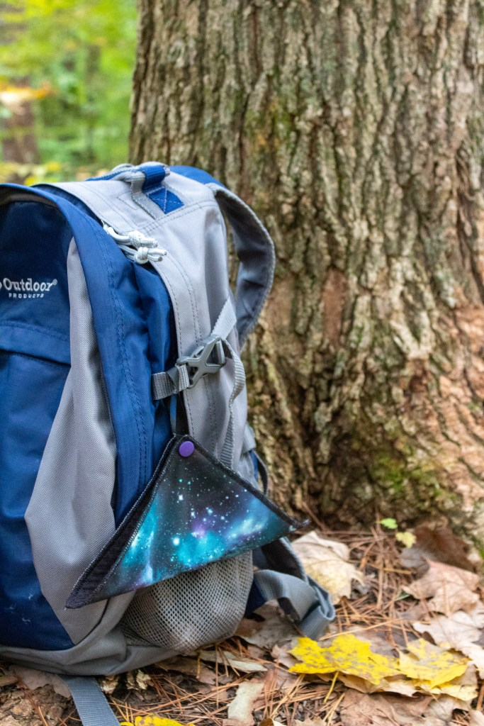 a hiking daypack with a kula cloth on the ground by a tree