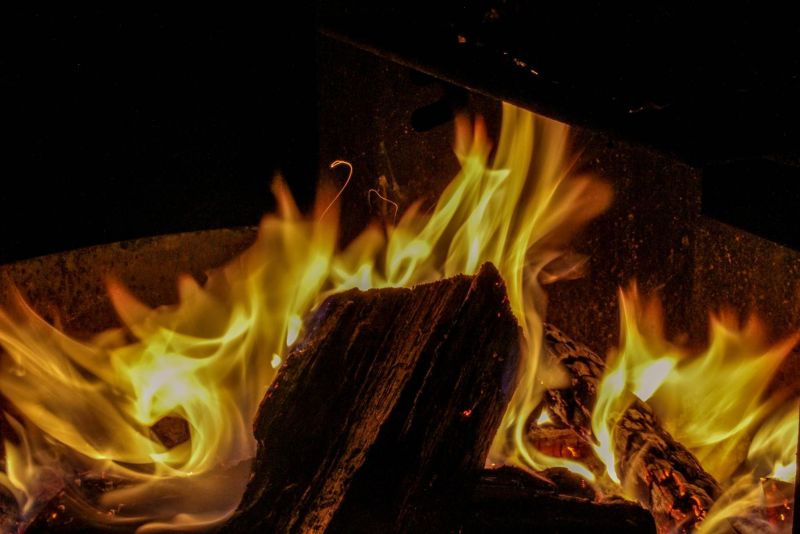 A campfire photo of a log surrounded by yellow and orange flames. Proper Campfire Etiquette