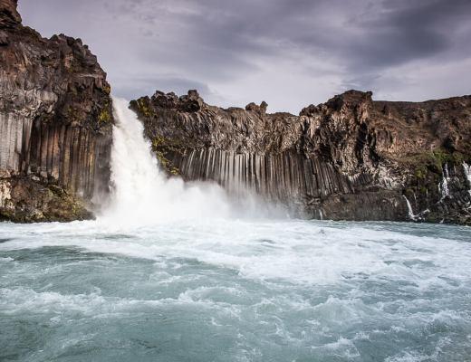 Waterval omringd door rotsen en water tijdens rondreis Noord-IJsland
