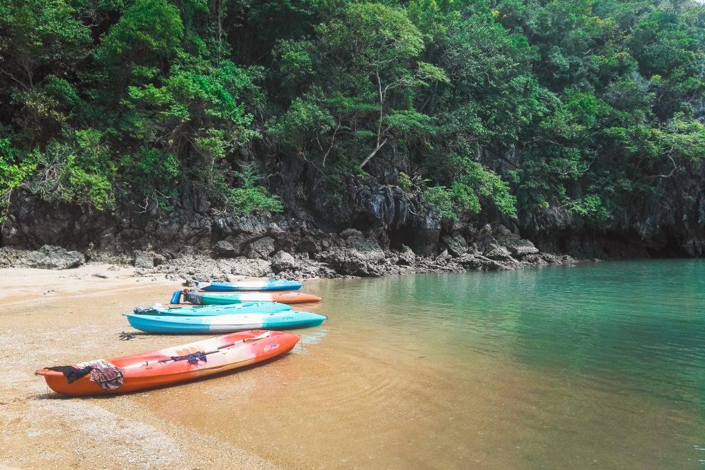 Gekleurde kano's op zandstrand bij blauw water.