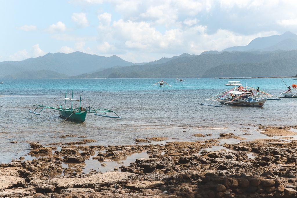 Vissersboten op blauw water bij rotsen Sabang.