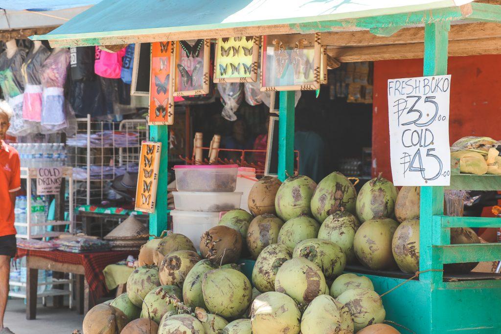Groene kokosnoten bij kleurrijk stalletje op straat.