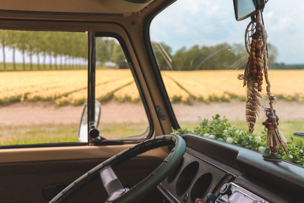 Uitzicht over stuur van Volkswagen Oldtimer over gele tulpenvelden.