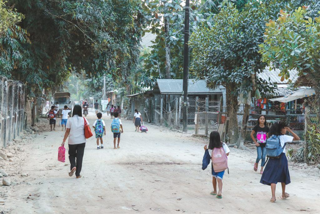 Stoffige straat met schoolkinderen Port Barton