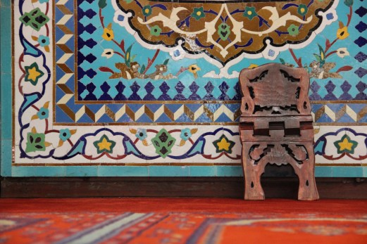 A Quran holder rests against one of the patterned tiles of the mihrab