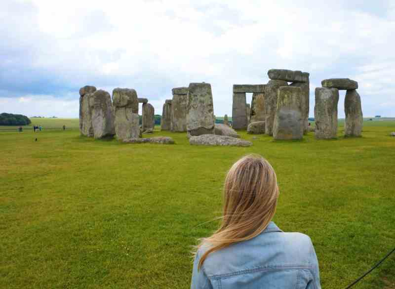 ellie quinn infront of stonehenge on a rainy and cloudy day