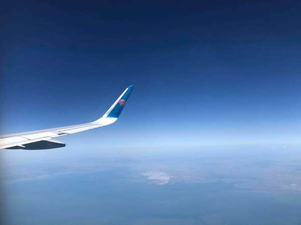 Southern China Airlines flight wing over the ocean