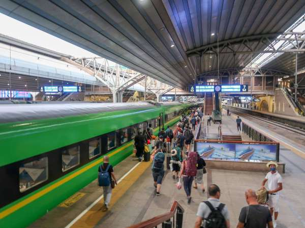 train travel in china, green train on platform in china train station
