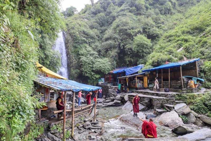 Bhagsu Waterfall base with monks by water | things to do in Bhagsu