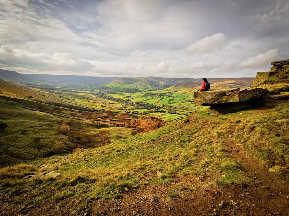 Peak District green fields and person sitting on rock | Peak District Day trip from London by train