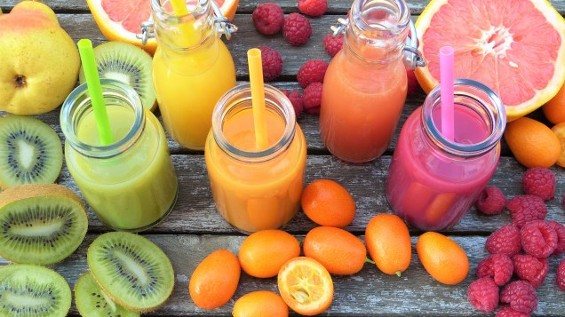 Four colorful smoothies with many whole fruits