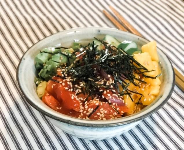 Poke Bowl with raw salmon and tuna, sliced cucumbers, chopped mango, sprinkled with sesame seeds and sliced nori