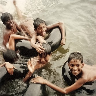The hands of joyous boys playing near a jetty, Kerala Bakwaters