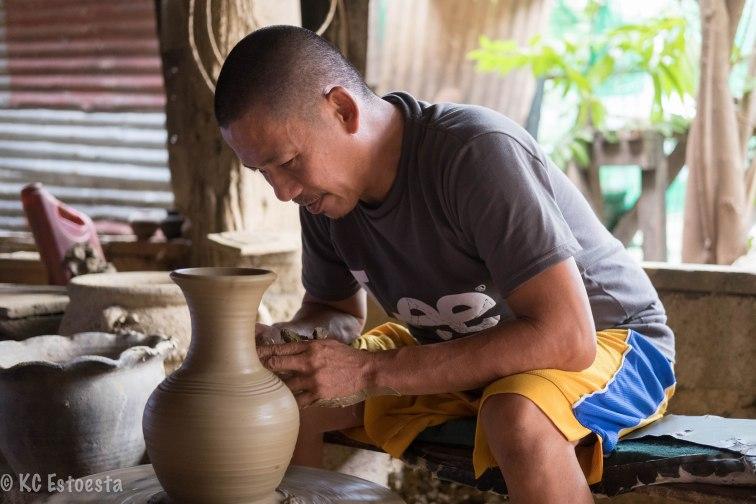 A potter finishes a basic burnay jar