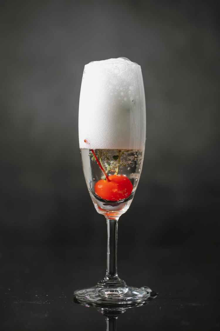 glass of sparkling champagne with berry