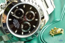 Hands-On Review: Rolex Cosmograph Daytona Stainless Steel ref. 116520 (Black) Rolex Daytona on left side sitting on green Rolex box with gold crown.
