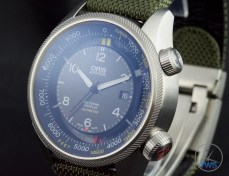 OrisBig Crown ProPilot Altimeter 47mm: Hands-On Review[01 733 7705 4134-07 5 23 14FC] - Watch sat up and facing the left reflecting blue light, time set to ten past ten, strap in the background