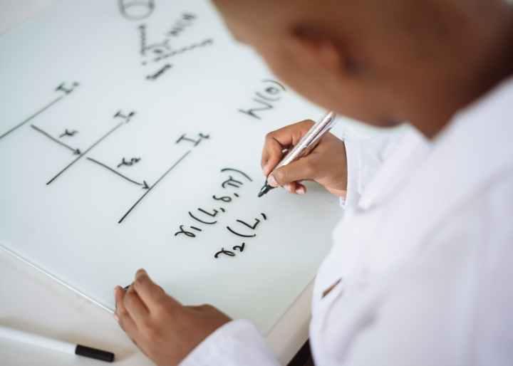 crop scientist using marker for deriving formulas on whiteboard