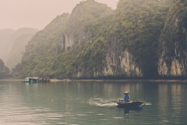 A fisherman leaves his floating village with the towering karsts as a backdrop in Halong Bay. Vietnam, February 2014.