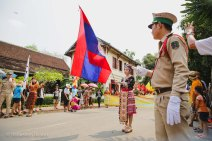 The Lao flag leads the traditional parade.