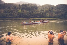 Our kayak guides take a bath while locals return home in the longtail water taxi. Nam Ou River, Laos, April 2014.