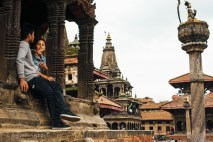A young couple chats near the wooden and brick temple structures of Patan's Durbar Square. Nepal, July 2014.