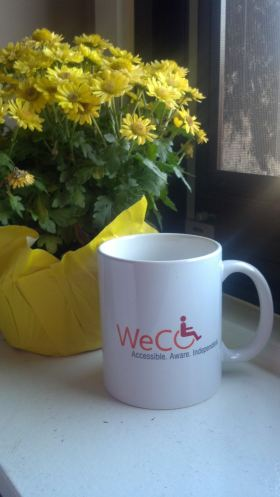 Photo of a WeCo logo mug on a widow sill next to a pot of yellow flowers.