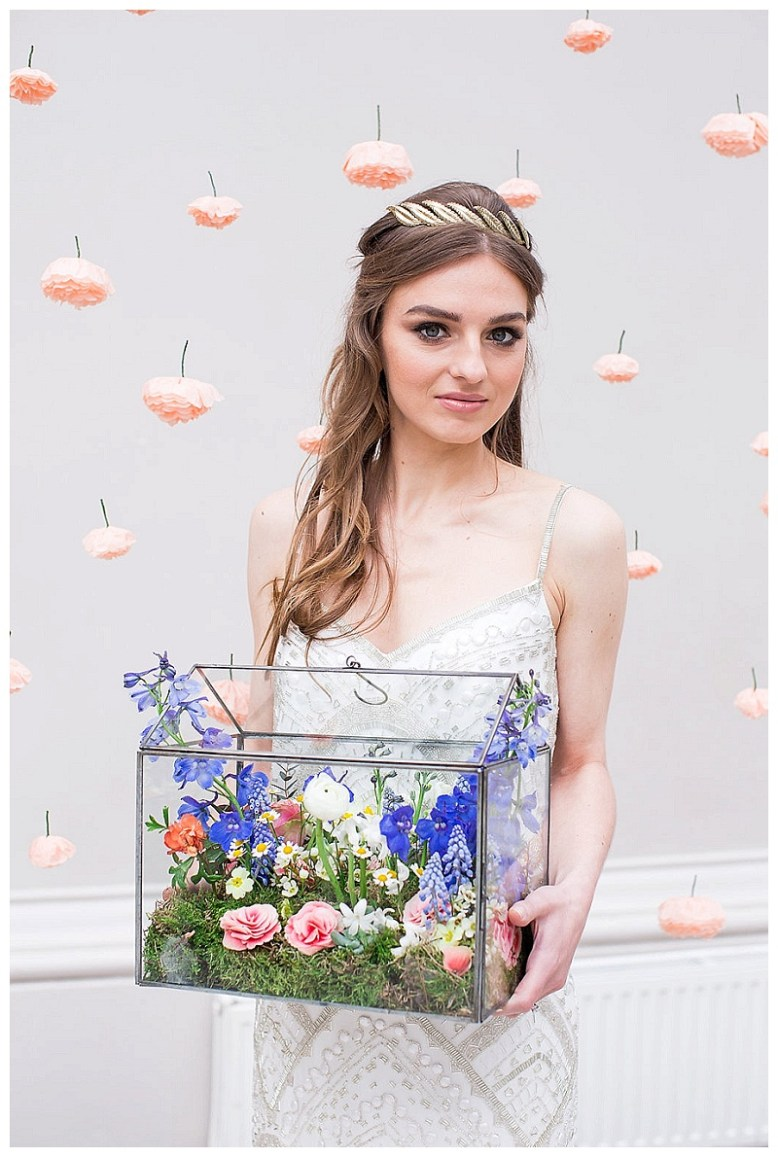 A bride stands in front of a paper flower backdrop holding a terrarium filled with flowers. She wears a beaded gown by Limor Rosen.