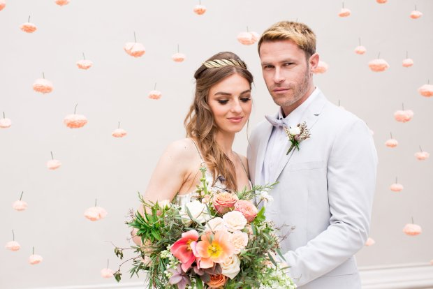 A couple stand in front of a handmade paper flower backdrop created by The Wedding Spark. The bride wears a Limor Rosen dress and carries a hand tied bouquet of peach, pink and coral blooms.
