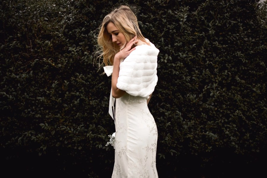 BB22 – faux fur bridal cape wrap shrug with a pretty satin bow on blonde bride with hair down