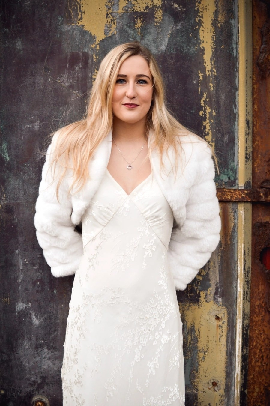 BB42 – faux fur cropped bridal jacket with sleeves on blonde bride with hair down in front of rusty door 2