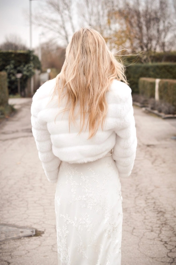 BB42 – faux fur cropped bridal jacket with sleeves on blonde bride with hair down on country lane back vire closeup