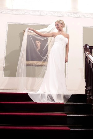Bride at the top of a grand staircase wearing one layer chapel length wedding veil