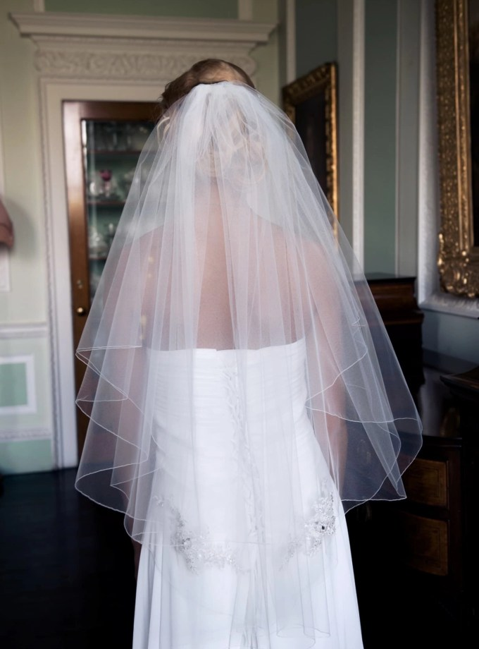 Bride wearing two layer bridal veil with lace appliques
