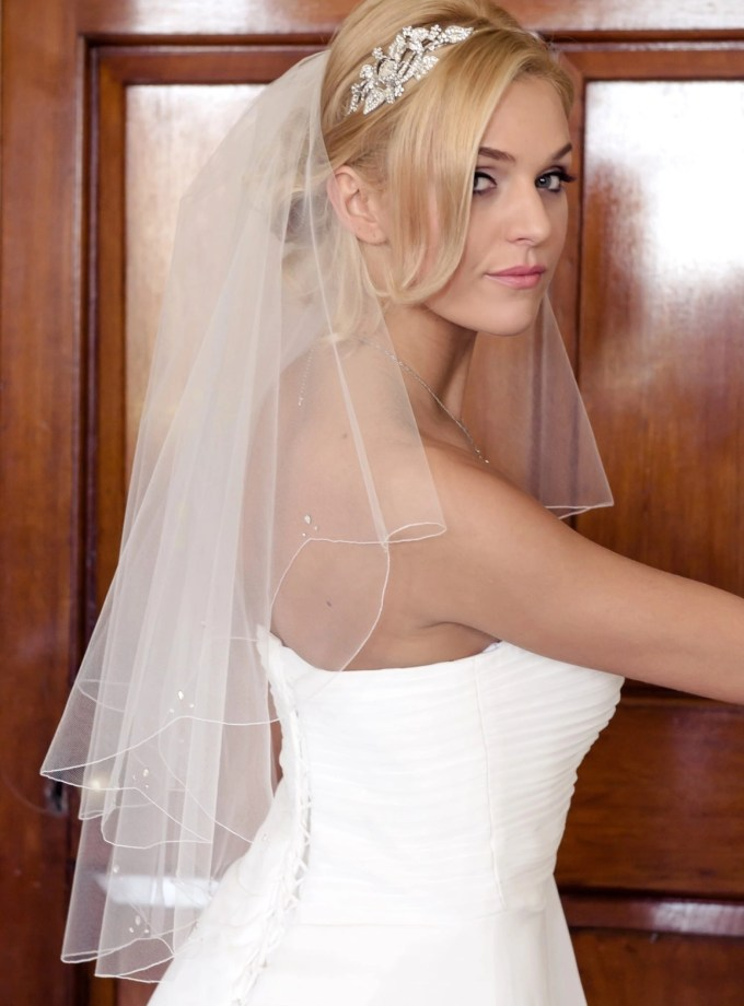 Bride looking over shoulder in short waist length veil