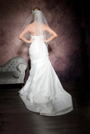 Bride with hands on hips wearing a wedding short veil with Ab crystals