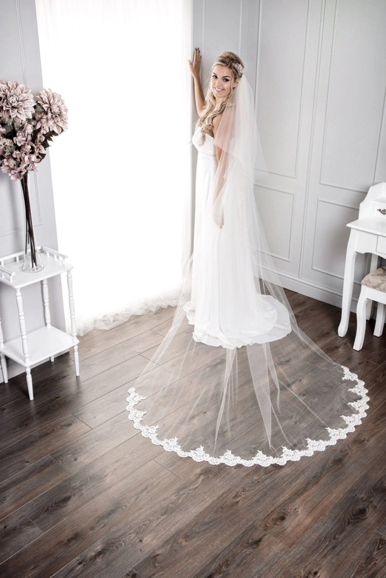 Bride wearing long chapel length veil with a lace bottom