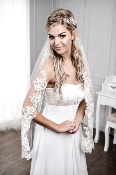 Bride wearing single layer fingertip length lace edge veil