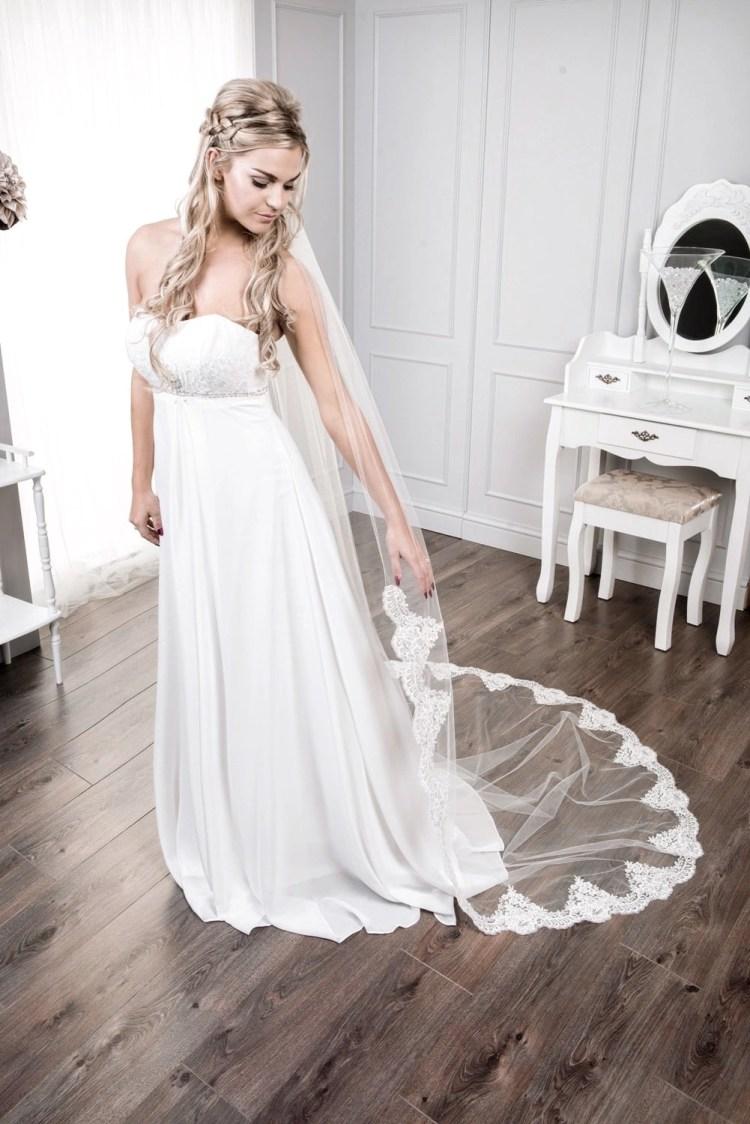 Bride wearing sparkly demi lace chapel length veil
