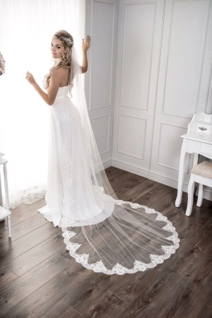 Bride at window wearing sparkly demi lace chapel length veil