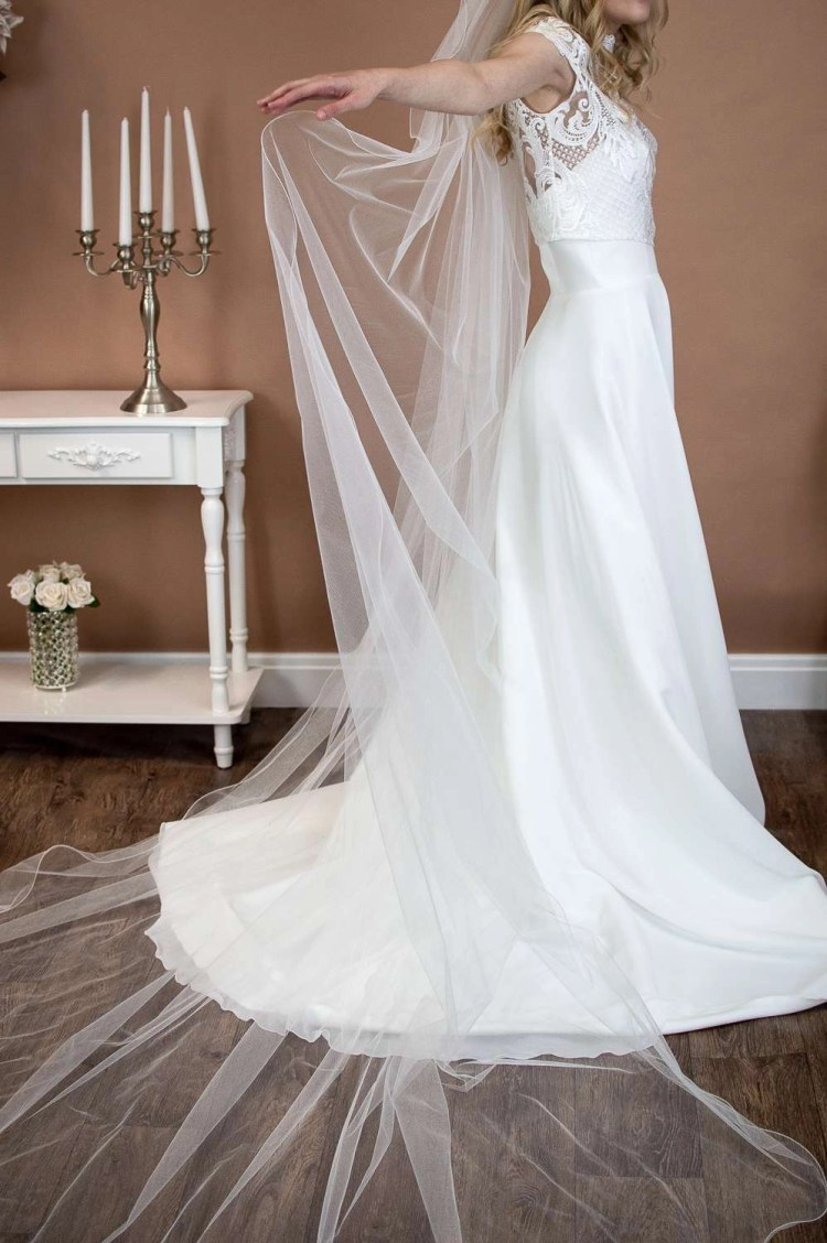 Isabella - one layer cathedral length extra wide veil with a wavy edge on a bride closeup side view