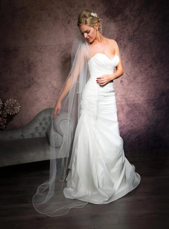 Bride posing in two layer floor length veil